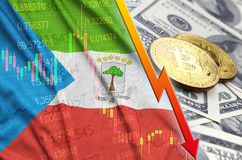 Equatorial Guinea flag and cryptocurrency falling trend with two bitcoins on dollar bills. Concept of depreciation Bitcoin in price against the dollar royalty free stock images