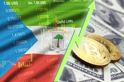 Equatorial Guinea flag and cryptocurrency growing trend with two bitcoins on dollar bills. Concept of raising Bitcoin in price against the dollar royalty free stock photos