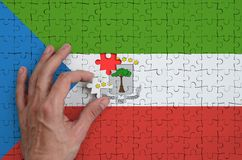 Equatorial Guinea flag is depicted on a puzzle, which the man`s hand completes to fold.  stock illustration