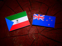 Equatorial Guinea flag with New Zealand flag on a tree stump iso. Lated stock images