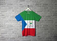 Equatorial Guinea flag on shirt and hanging on the wall with brick pattern wallpaper. Green white and red with a blue triangle and the National Coat of arms royalty free stock image