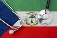 Equatorial Guinea flag and stethoscope. The concept of medicine. Stethoscope on the flag in the background royalty free stock images