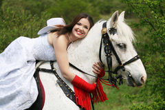 Equestrian. The young bride sits astride a white horse and embraces her for a neck Stock Photos