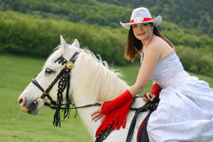 Equestrian. The young bride sits astride a white horse and embraces her for a neck Stock Photography
