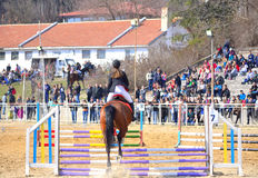 Equestrian competition horse jumping Varna Bulgaria. Back view of equestrian girl jumping brown horse over rails during the equestrian competition for junior and stock image