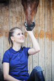 Equestrian girl and horse in stable Royalty Free Stock Images