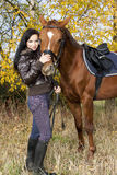 Equestrian with her horse. In autumnal nature Royalty Free Stock Photos