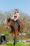Equestrian - Horse Jumping. Pretty girl and bay horse during the sunny day Royalty Free Stock Photos