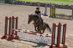 Equestrian, horse jumping. Bromont june 14, 2015 picture of young woman jumping hurdle with brown horse during competition Stock Photos