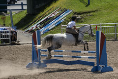 Equestrian, horse jumping. Bromont june 14, 2015 side view of young woman jumping hurdle with horse during competition Royalty Free Stock Images
