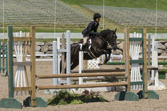 Equestrian - horse jumping. Bromont june 14, 2015 a young woman horse rider jumping a hurdle with his beautiful dark brown sport horse in a competition of an Stock Photography