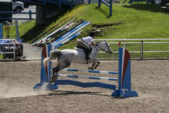 Equestrian - horse jumping. Bromont june 14, 2015 a young woman horse rider jumping a hurdle with his beautiful white sport horse in a competition of an Royalty Free Stock Photos