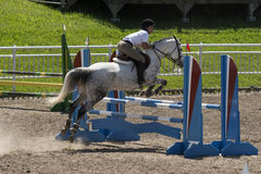 Equestrian - horse jumping. Bromont june 14, 2015 a young woman horse rider jumping a hurdle with his beautiful white sport horse in a competition of an Royalty Free Stock Images
