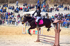 Equestrian horse jumping. Equestrian girl jumping a horse over rails during the  equestrian competition for junior and young riders on the occasion of Todorovden Royalty Free Stock Image