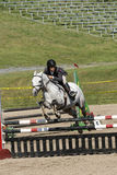 Equestrian - horse jumping. Picture of rider and white horse jumping during competition at the bromont concours June 12, 2016 Royalty Free Stock Image