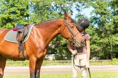 Equestrian joven del adolescente que besa sus hors preferidos de la castaña Fotos de archivo