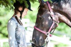 Equestrian joven del adolescente que toca su nariz del caballo de la castaña Fotografía de archivo