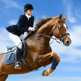 Equestrian jumper. Young girl jumping with sorrel horse Stock Photo