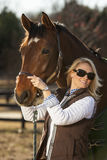 Equestrian Model and Horses. A blonde equestrian model feeds her horses in an outdoor environment Stock Photo