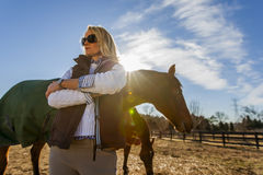 Equestrian Model and Horses. A blonde equestrian model feeds her horses in an outdoor environment Royalty Free Stock Photography