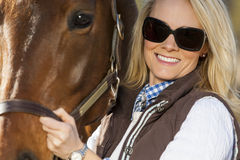 Equestrian Model and Horses. A blonde equestrian model feeds her horses in an outdoor environment Stock Photos