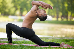 Equestrian pose with garudasana hands. Profile of sporty Indian young man warming up, doing stretching exercises, standing in low lunge on river bank in park stock photos