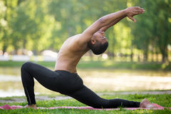 Equestrian pose. Profile of sporty Indian young man practicing yoga, fitness, pilates on riverbank in park, doing low lunge exercise on river bank in park, full stock photography