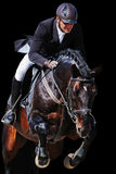 Equestrian: rider with bay horse in jumping show, isolated. On black background Royalty Free Stock Images
