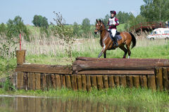 Equestrian sport. Cross-coutry. Woman on horse is Drop fence in Water jump Royalty Free Stock Photos