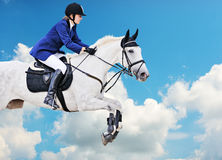 Equestrian sport: young girl in jumping show. On the background of blue sky Stock Photography