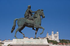 Equestrian statue of louis xiv at place bellecour. View of the equestrian statue of louis xiv and the basilica of notre dame de fourviere from place bellecour Royalty Free Stock Photos