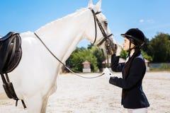 Equestrianism cariñoso de la mujer delgada hermosa que mira el caballo blanco fotografía de archivo