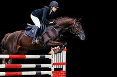 Equestrianism: Ung flicka i banhoppningshowen som isoleras på svart Arkivfoton