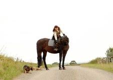Equestrienne con el perro en el fondo blanco. Foto de archivo