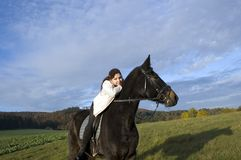Equestrienne and horse. Horsewoman lay down on the withers of the horse Royalty Free Stock Photography