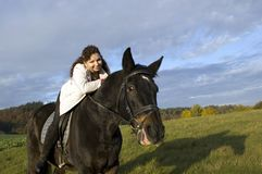 Equestrienne and horse. Horsewoman lay down on the withers of the horse Royalty Free Stock Images