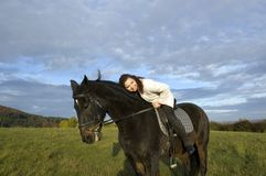 Equestrienne and horse. Horsewoman lay down on the withers of the horse Stock Images