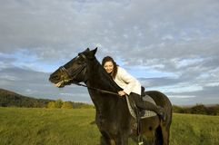 Equestrienne and horse. Horsewoman lay down on the withers of the horse Stock Photos