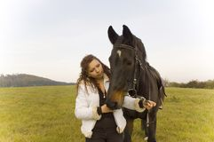 Equestrienne and horse. Horsewoman holds the horse's bridle Royalty Free Stock Photography