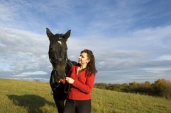 Equestrienne and horse. The woman and the horse are on the field on a  background of the cloudy sky Stock Image