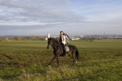 Equestrienne rides. Horsewoman rides a horse across the field Royalty Free Stock Photo