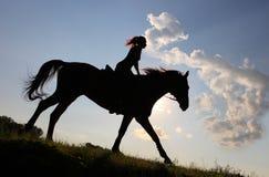 Equetsrian ехать ее лошадь на заходе солнца Стоковое Изображение