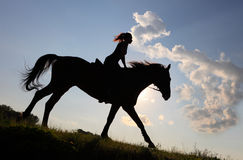 Equetsrian riding her horse at sunset Stock Image