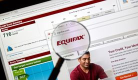 Equifax official site and logo under magnifying glass stock photography