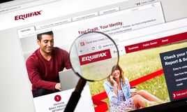 Equifax official site and logo under magnifying glass royalty free stock images
