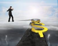 Equilíbrio do homem de negócio na borda da mão de pulso de disparo no pico de montanha Fotografia de Stock Royalty Free