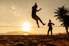 Equilíbrio dos adolescentes na silhueta do slackline Fotografia de Stock