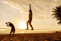 Equilíbrio dos adolescentes na silhueta do slackline Imagens de Stock