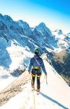 Equilíbrios alpinos do montanhista no snowfield do gelo Foto de Stock