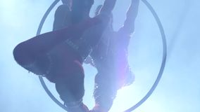 Equilibrador fêmea no cair para trás de encontro bege da malha na aro aérea no fundo preto Silhueta Movimento lento Fim acima video estoque